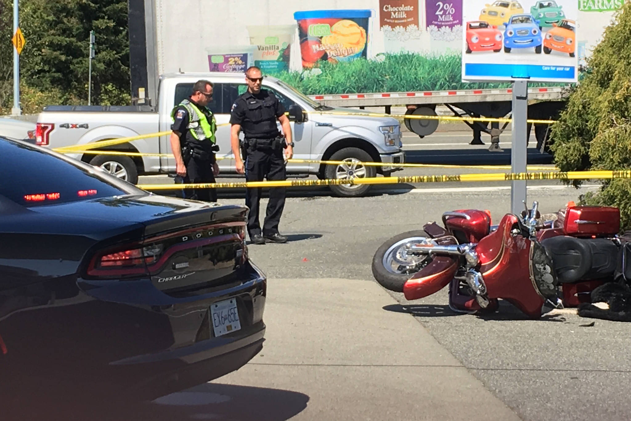 A motorcycle sits on its side and Saanich police officers keep an eye on the scene after a crash at Tillicum Road and the Trans-Canada Highway on Thursday. (Devon Bidal/News Staff)